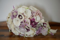 Cascading wedding bouquet with calla lilies, purple roses, decorated with silver jewelry, silk and pearl beads rested on a wooden royalty free stock image