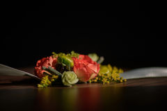 Wedding floral centerpiece with red rose at its core against a dark background Stock Photos