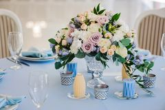 Wedding art decor. Wedding hall in the restaurant with tables decorated with cloth of blue and pink bouquet of roses and blue delphinium. glasses cutlery candles Stock Image