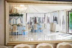 Wedding art decor reflection. Wedding hall in the restaurant with tables decorated view mirror or reflection Stock Photos