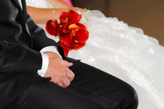 Wedding atmosphere. Groom hands on wedding with red flowers bridal bouquet in background Royalty Free Stock Image