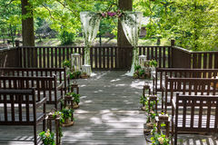 Wedding attributes. Wedding ceremony. White pillars of a wedding arch, decorated with flowers, and brown benches. Horizontal frame. Wedding attributes. Wedding Stock Photo