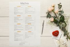 Bridal background with planner checklist. Wedding background with checklist. Paper planner and wedding rings on white wooden table with tender bridal bouquet stock photos