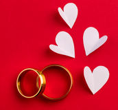 Wedding background - two gold wedding rings and handmade hearts Royalty Free Stock Images