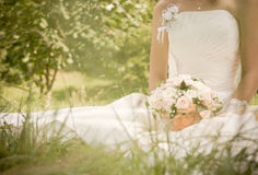 Wedding backgrouund. Young beautiful bride with wedding bouquet on the grass royalty free stock photo