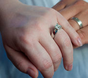 Wedding Band Hands. A Caucasian couple wearing their wedding rings and holding each others hands. Their wedding bands are white gold and glisten in the light royalty free stock image