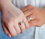 Wedding Band Hands. A Caucasian couple wearing their wedding rings and holding each others hands. Their wedding bands are white gold and glisten in the light stock photo