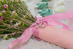 Wedding Band on Pink Ribbon Floral Bouquet. This is an image created using a floral bouquet, wedding bands, and also a white background royalty free stock photo