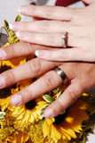Wedding Bands. Bride and groom hands are posed together over bouquet of yellow sun flowers.  Rings are clearly visible Royalty Free Stock Photo