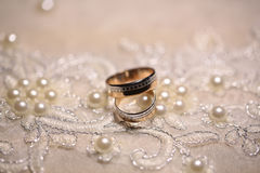 Wedding bands on embroidered cloth Royalty Free Stock Photos