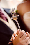 Wedding Bands On a Fork. Happy Bride and Groom Holding wedding bands on a silver fork stock photo