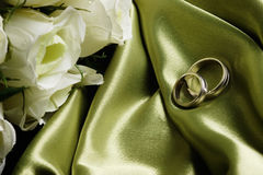 Wedding bands on green satin Royalty Free Stock Photos