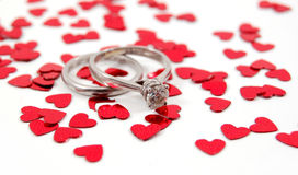 Wedding Bands and Hearts. Platinum wedding bands on a white background with red hearts stock image