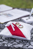 Wedding Bands on Lace Pillow. Pair of wedding bands on a white lace pillow with a red satin ribbon at an outdoor wedding Stock Image