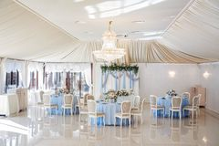 Wedding banquet before ceremony. Wedding hall in the restaurant with tables decorated with cloth of blue and pink bouquet of roses and blue delphinium. elegant Stock Photography