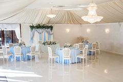 Wedding banquet before ceremony. Wedding hall in the restaurant with tables decorated with cloth of blue and pink bouquet of roses and blue delphinium. elegant Royalty Free Stock Image