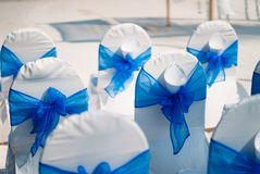 Wedding banquet chair cover in blue theme. The wedding decoration of the beach wedding venue, the chairs with banquet in white and blue theme Royalty Free Stock Photo