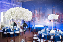 Wedding. Banquet. The chairs and round table for guests, served with cutlery and crockery and covered with a blue Stock Images