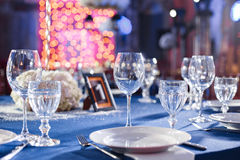 Wedding. Banquet. The chairs and table for guests, served with cutlery and crockery and covered with a blue tablecloth. Wedding. Banquet. The chairs and table Royalty Free Stock Photos