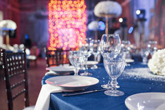 Wedding. Banquet. The chairs and table for guests, served with cutlery and crockery and covered with a blue tablecloth. Wedding. Banquet. The chairs and table Royalty Free Stock Photo