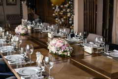 Wedding Banquet or gala dinner. The chairs and table for guests, served with cutlery and crockery. Wine glasses in the foreground. Wedding Banquet or gala stock photos