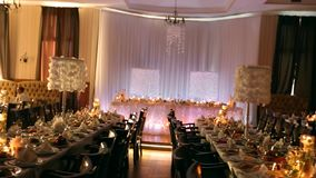 Wedding banquet hall interior details with decorated table setting at restaurant. Candles and white petals decoration. Wedding banquet hall interior details stock footage