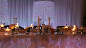Wedding banquet hall interior details with decorated table setting at restaurant. Candles and white petals decoration. Wedding banquet hall interior details stock video