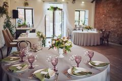 Wedding banquet, loft style, served tables with flowers and lots of greenery stock image