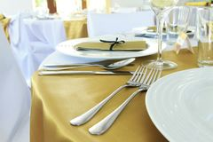 Wedding banquet. Wedding ornated table with fork and spoon, plates and golden table-cloth Stock Images