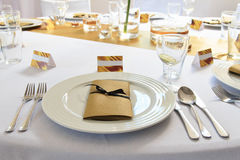 Wedding banquet. Wedding ornated table with fork and spoon, plates on white  table-cloth Stock Image