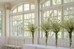 Wedding Banquet Room. At the Crescent Hotel in Eureka Springs, Arkansas.  Four beautiful white and green floral arrangements in front of cottage style windows Stock Images