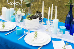 Wedding banquet table. Cake with white cream decorated with blueberry and greenery. Cutlery with stemware plates and candles on a Stock Photos