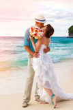Wedding. Bbride and groom kissing on the tropical coast at sunse Stock Images