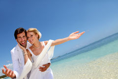 Wedding by the beach. Married couple standing by blue lagoon Stock Photography