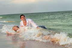Wedding on beach. Bride and Groom lying in beach shore Stock Image