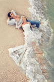 Wedding on beach. Bride and Groom lying in beach shore Royalty Free Stock Photography