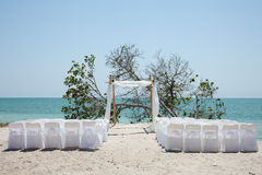 Wedding on the beach, chairs and chuppa. Rows of chairs and a canopy arbor (chuppa) arranged on the beach in preparation for a wedding ceremony Stock Image