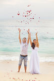 Wedding on the beach. Happy couple with flower petals Royalty Free Stock Images
