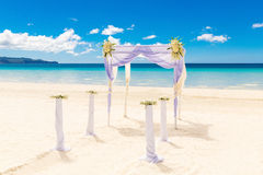 Wedding on the beach . Wedding arch decorated with flowers on tr Royalty Free Stock Photo