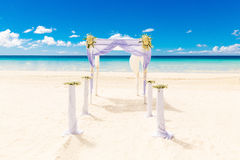 Wedding on the beach . Wedding arch decorated with flowers on tr Royalty Free Stock Photography