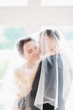 Wedding.Beautiful bride and groom portrait with veil over face. Stylish Loving wedding couple kissing and hugging. Wedding day.Beautiful bride and groom portrait Stock Photography