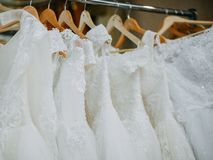 Wedding dresses on hangers. Wedding beautiful white dresses on wooden light brown hangers royalty free stock images