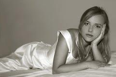 Wedding beauty. Beauty girl is lying on white dress Royalty Free Stock Photography