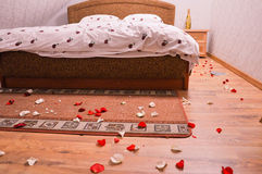 Wedding bed. Ready wedding bed for the new couple with champagne and rose leaves all over the room Royalty Free Stock Photos