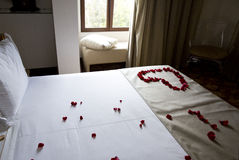 Wedding bed topped with rose petals Stock Photo