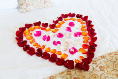 Wedding bed topped with rose petals Stock Image