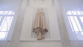 Wedding beige dress hanging on wall inside space room in big house stock footage