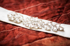 Wedding belt decorated with jewelry on red sofa. Marriage concept Royalty Free Stock Photography