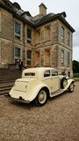 Wedding at Belton house. A beautiful cream Rolls Royce sits outside Belton house near grantham with the chauffeur awaiting the bride and groom Stock Photo