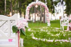 Wedding benches and flower arch for ceremony. Wedding benches and flower arch for a wedding ceremony outdoors Royalty Free Stock Photography